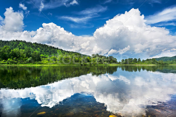 Beautiful landscape with cloudy blue sky reflected in the clear  Stock photo © TasiPas
