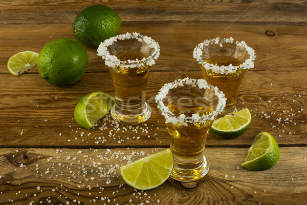 Three tequila shots with lime and salt on the wooden background Stock photo © TasiPas