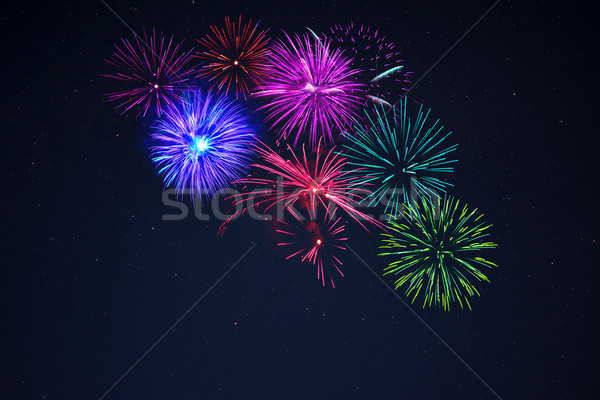 Pink purpe blue green fireworks over starry sky Stock photo © TasiPas