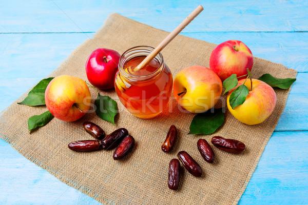 Glass  honey jar, dates and apples on burlap napkin Stock photo © TasiPas