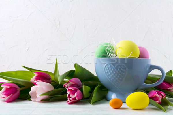 Easter hand painted eggs in blue cup and pink tulips background Stock photo © TasiPas
