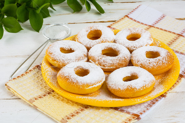 Delicious donuts on yellow plate Stock photo © TasiPas