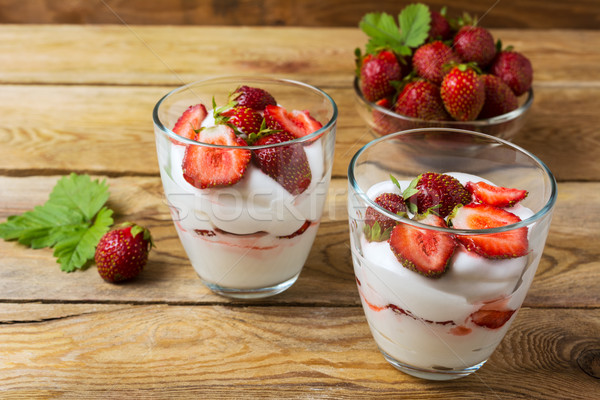 Summer layered cream cheese dessert and strawberry in glass bowl Stock photo © TasiPas