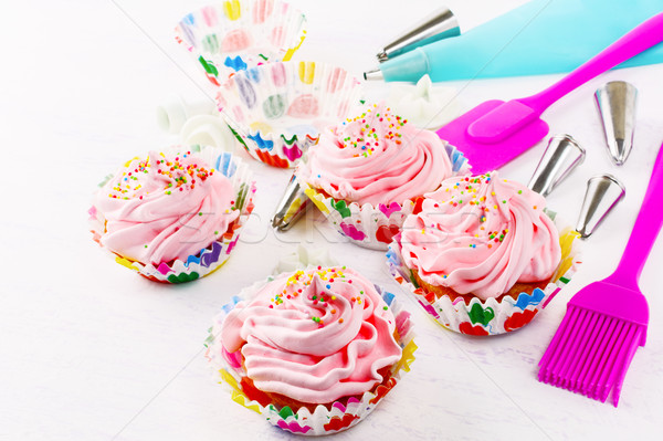 Swirl cupcake with whipped cream frosting and confectionery syri Stock photo © TasiPas
