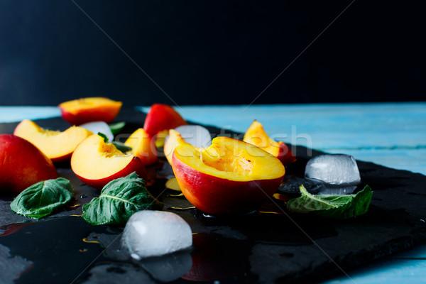 Szeletek érett őszibarackok fekete kő friss gyümölcs Stock fotó © TasiPas