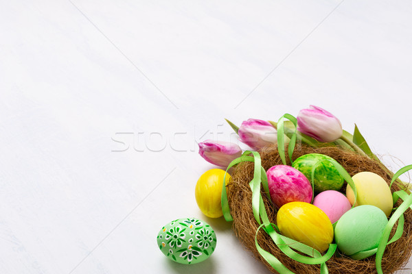 Easter centerpiece with painted eggs in the nest and silk ribbon Stock photo © TasiPas