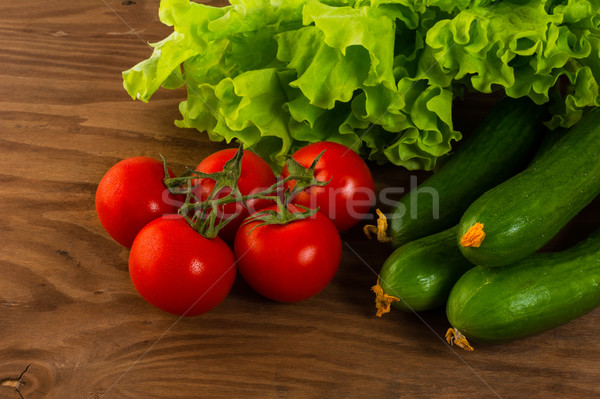 Cucumber and cherry tomato on wooden background Stock photo © TasiPas