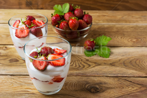 Whipped cream with strawberry on wooden background Stock photo © TasiPas