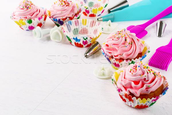 Cookware and pink birthday cupcakes  Stock photo © TasiPas