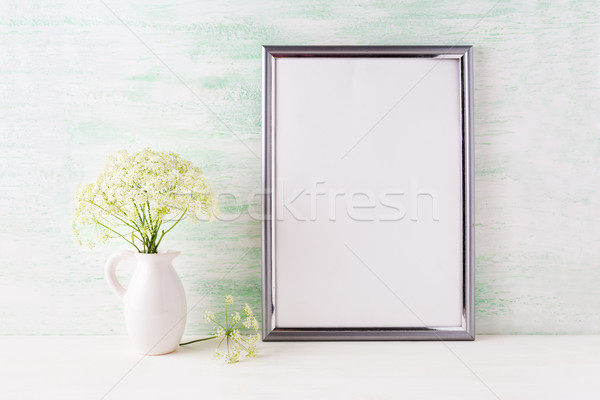 Silver frame mockup with delicate wild field flowers in pitcher Stock photo © TasiPas
