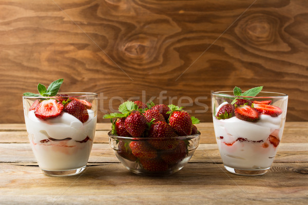 Strawberries dessert with whipped cream on rustic wooden backgro Stock photo © TasiPas