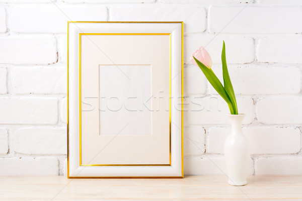 Gold decorated frame mockup with pale pink tulip in vase Stock photo © TasiPas
