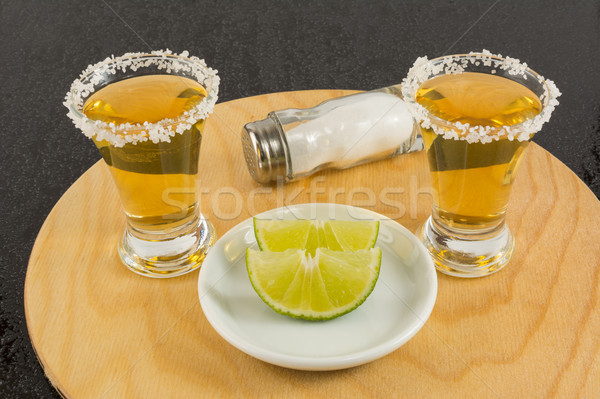 Shots of gold tequila on the wooden tray Stock photo © TasiPas