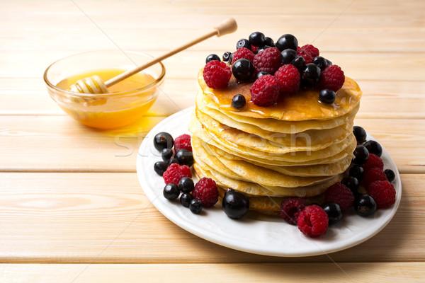Homemade pancakes with honey and fresh berries Stock photo © TasiPas