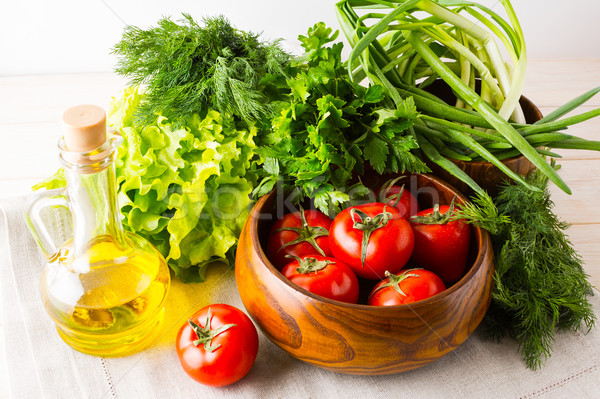 Olive oil, garlic and tomato in wooden bowl Stock photo © TasiPas