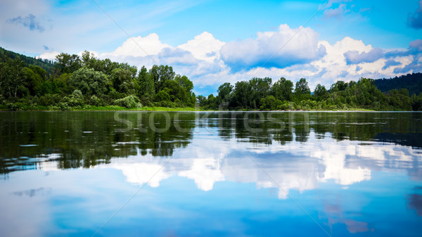 Beautiful landscape panorama with cloudy blue sky reflected in t Stock photo © TasiPas