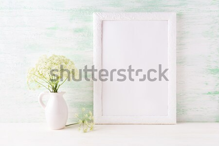 White frame mockup with delicate wild field flowers in pitcher Stock photo © TasiPas