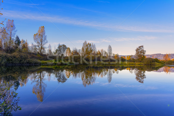 Beautiful fall landscape with blue sky reflected in the water Stock photo © TasiPas
