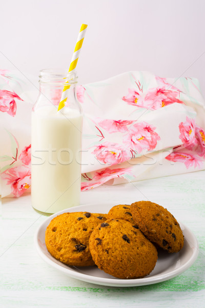 Milk bottle and cookies on white plate, vertical Stock photo © TasiPas