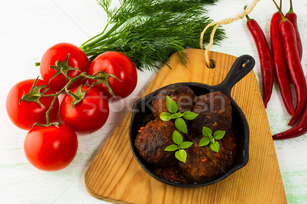 Grilled meatballs with chili pepper and tomato served in cast ir Stock photo © TasiPas