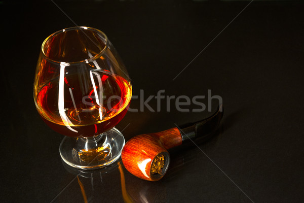 Whiskey glass and smoking pipe on black background Stock photo © TasiPas