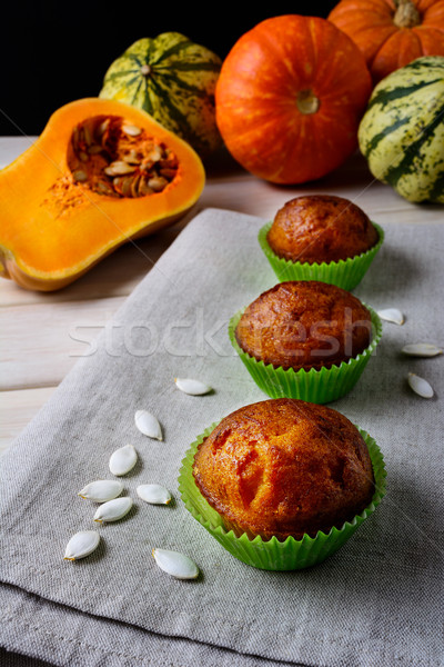 Pumpkin muffins in the green wrappers with squash seeds Stock photo © TasiPas