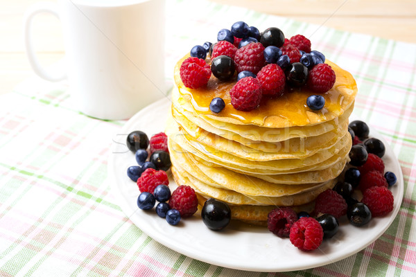 Breakfast pancakes with honey and fresh berries on the white pla Stock photo © TasiPas