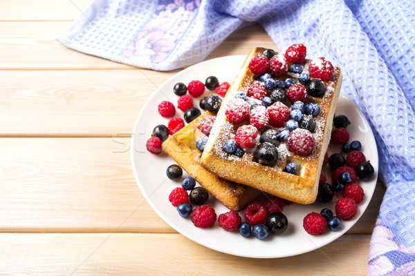 Soft waffle with blueberry and raspberry on blue linen napkin Stock photo © TasiPas