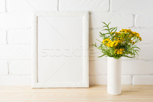 White frame mockup with yellow flowers near painted brick walls Stock photo © TasiPas