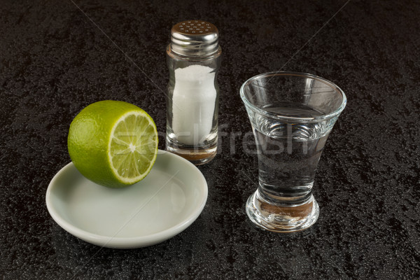 Silver tequila with lime on black background Stock photo © TasiPas