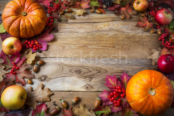 Frame of pumpkins, apples, acorns, berries and fall leaves on wo Stock photo © TasiPas