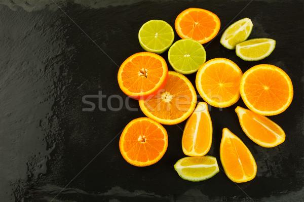Limes, oranges and lemons on black background, copy space Stock photo © TasiPas