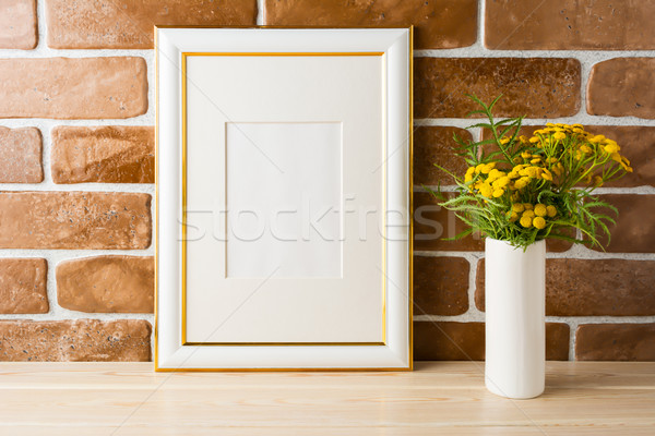 Gold decorated frame mockup  yellow flowers near exposed brick w Stock photo © TasiPas