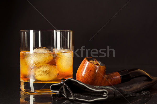 Scotch drink glass and smoking pipe on black background Stock photo © TasiPas