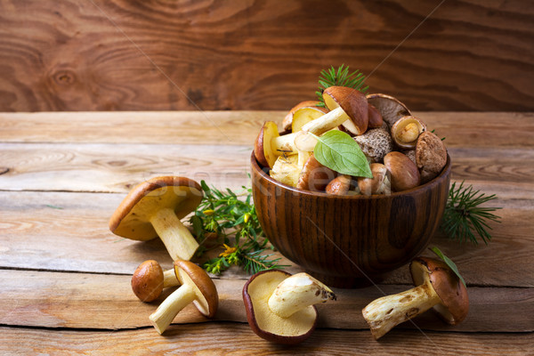 Edible mushrooms in the wooden bowl Stock photo © TasiPas