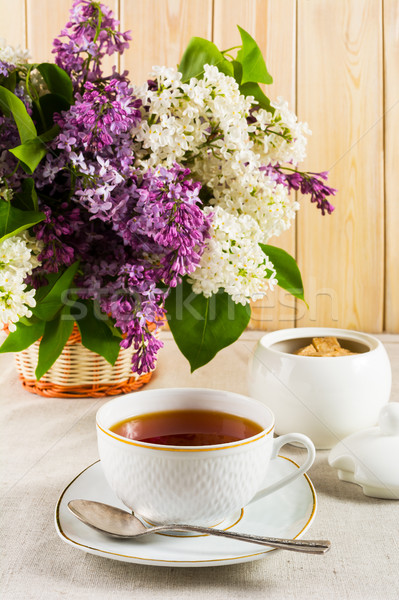 Cup of tea and branch of lilac flower in wicker basket on linen  Stock photo © TasiPas