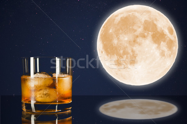 Whiskey glass on midnight sky with full moon background.  Stock photo © TasiPas