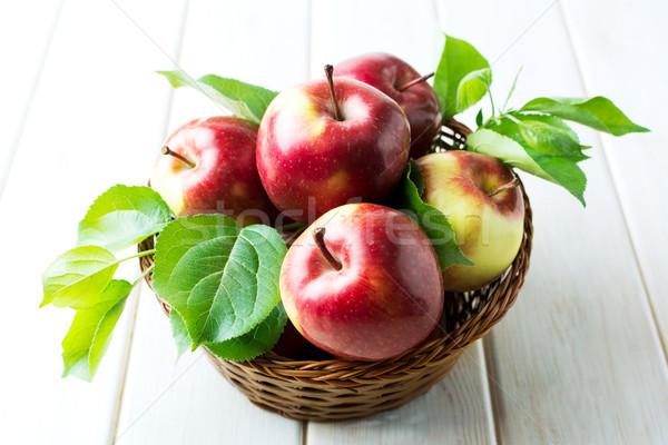 Organikus piros almák zöld levelek fonott kosár Stock fotó © TasiPas