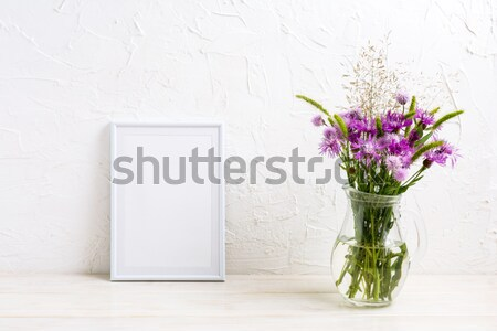 White frame mockup with purple burdock in the glass jug Stock photo © TasiPas