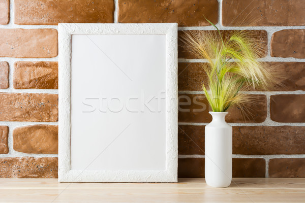 White frame mockup with ornamental grass near exposed brick wall Stock photo © TasiPas