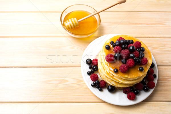 Breakfast pancakes with honey and fresh berries Stock photo © TasiPas