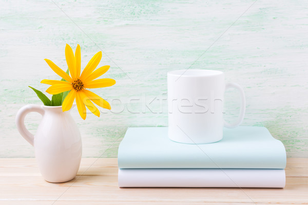 White coffee mug mockup with golden yellow rosinweed in pitcher Stock photo © TasiPas