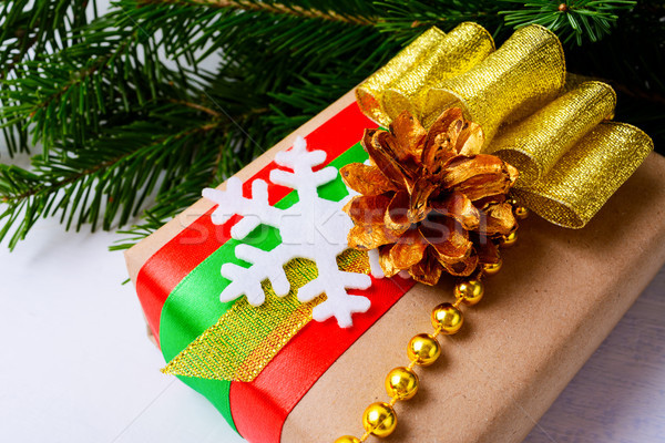Christmas gift box with golden ribbon, pine cone and beads Stock photo © TasiPas