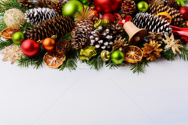 Christmas greeting card with pine cones and wooden jingle bell Stock photo © TasiPas