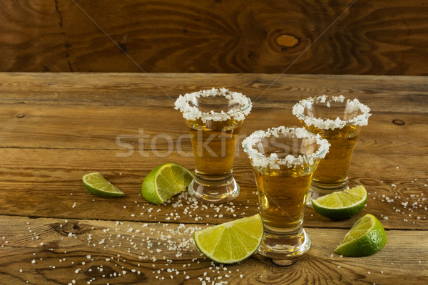 Three shots of gold tequila  on the wooden background Stock photo © TasiPas
