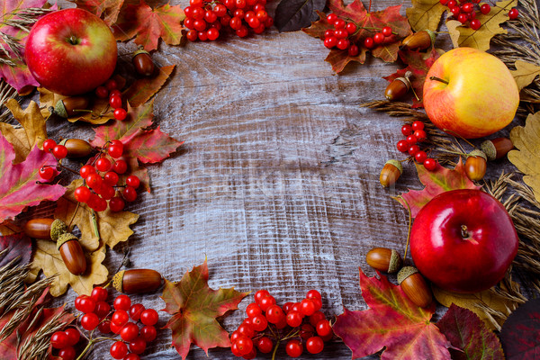 Frame of apples, acorns, berries and fall leaves on the rustic w Stock photo © TasiPas