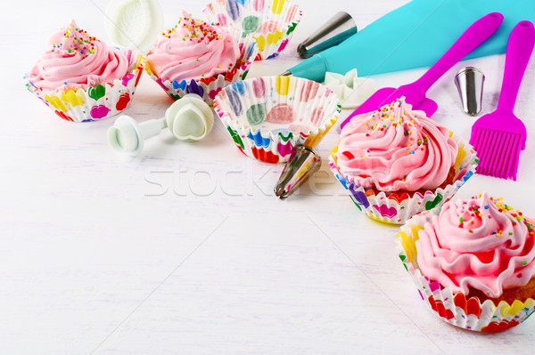 Cookware and cupcakes with pink whipped cream swirl, copy space Stock photo © TasiPas