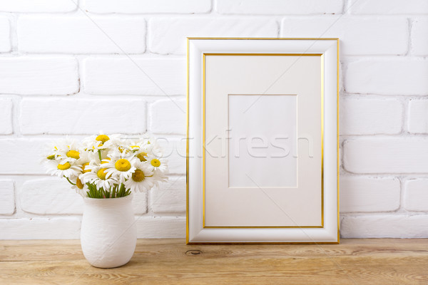 Gold decorated frame mockup with chamomile bouquet in rustic vas Stock photo © TasiPas