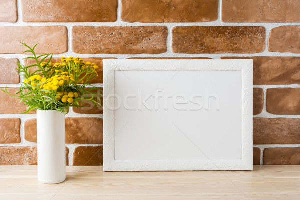 White landscape frame mockup with yellow flowers near exposed br Stock photo © TasiPas