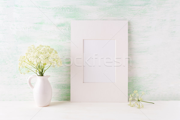 Easy white frame mockup with tender wild flowers in pitcher Stock photo © TasiPas